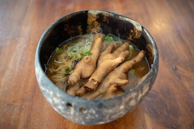 A sopa tailandesa dos pés da galinha com macarronete serviu em uma bacia tailandesa do coco.