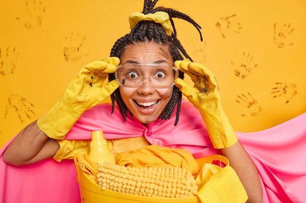 A super-heroína profissional usa luvas de proteção, capa e luvas de borracha, observa cuidadosamente as poses da câmera perto do cesto de roupa suja isolado sobre a parede amarela
