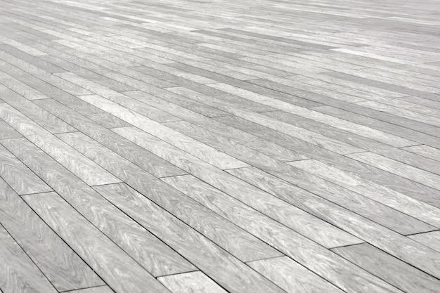 A superfície com ladrilhos de pedra retangulares alongados de cor cinza entra em perspectiva diagonal