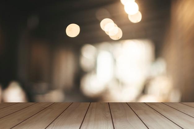 A superfície da mesa de madeira vazia e o fundo desfocado da cozinha no café.