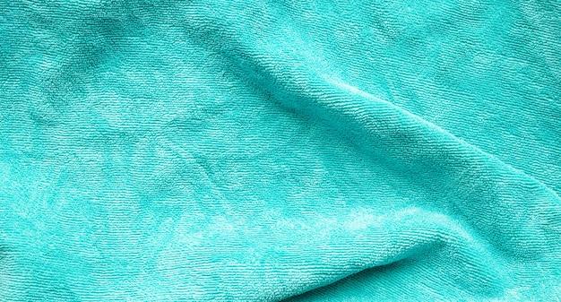 A superfície da textura do tecido de toalha verde fechar o fundo