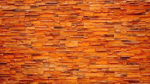 A superfície das antigas paredes de tijolo marrom e vermelho