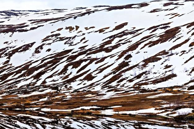 A superfície das montanhas nas fendas e cobertas de neve