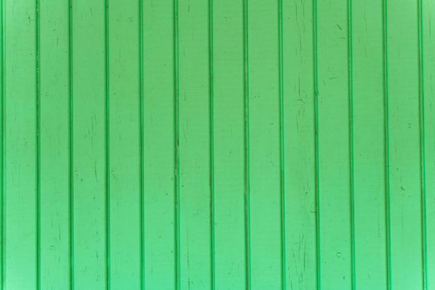 A superfície das ripas de madeira é pintada de verde.