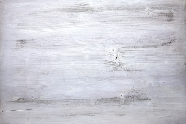 A superfície de uma madeira velha casualmente pintada com tinta branca.