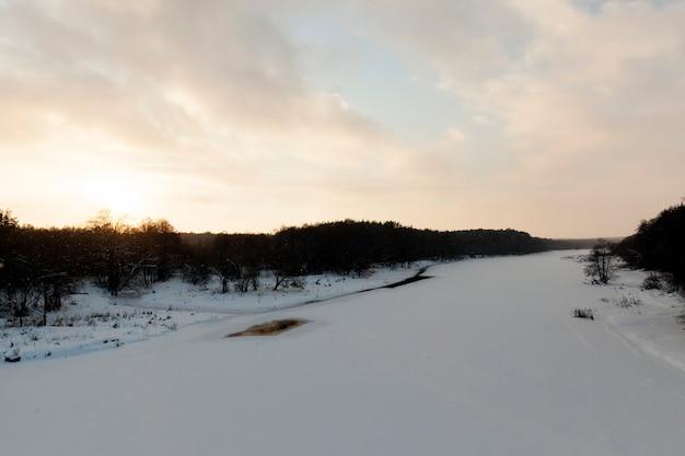 A superfície do rio coberta de gelo e neve ao pôr do sol, congelada no inverno