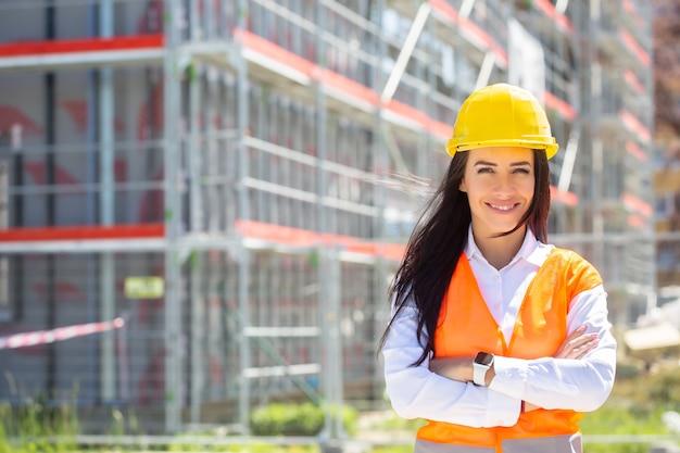 A supervisora feminina do local, usando colete de segurança e capacete, fica de pé com segurança na frente da construção, coberta por andaimes.