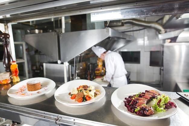 A tabela de distribuição na cozinha do restaurante. o chef prepara uma refeição no fundo dos pratos acabados.