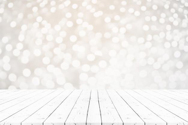 A tabela de madeira branca vazia da perspectiva na parte superior sobre o fundo do borrão, pode ser usado zomba acima.