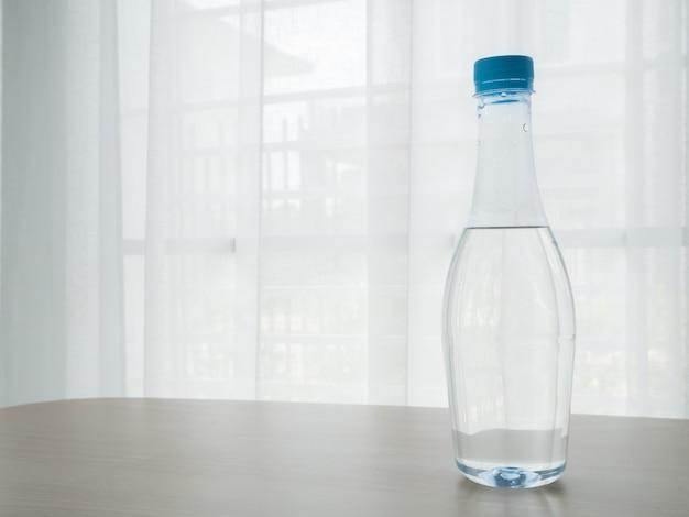 A tabela de madeira com a garrafa da água no branco bonito obscuro drapeja o fundo da textura da janela.