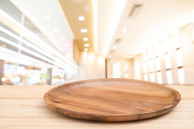 A tabela de madeira da perspectiva e a bandeja de madeira na parte superior sobre o backgrounk claro do bokeh do borrão podem ser nós