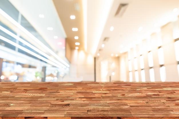 A tabela de madeira da perspectiva na parte superior sobre o fundo da cafetaria do borrão, pode ser usado para