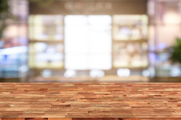 A tabela de madeira da perspectiva na parte superior sobre o fundo da cafetaria do borrão, pode ser usado zomba acima.