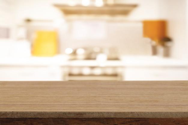 A tabela de madeira vazia da perspectiva na parte superior sobre o fundo do borrão, pode ser usada para a exposição dos produtos da montagem