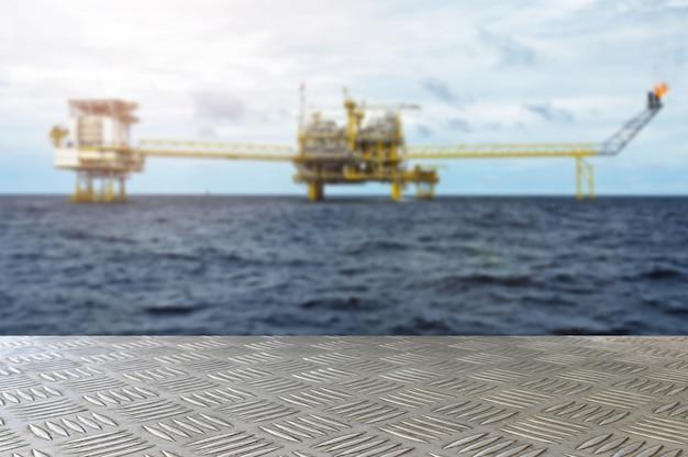 A tabela vazia da placa do ferro com plataforma de petróleo e gás ou plataforma offshore de construção da plataforma desfoca o fundo para apresentação e advertorial.