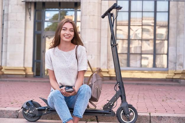 À tarde, uma jovem sorridente se senta em uma scooter elétrica