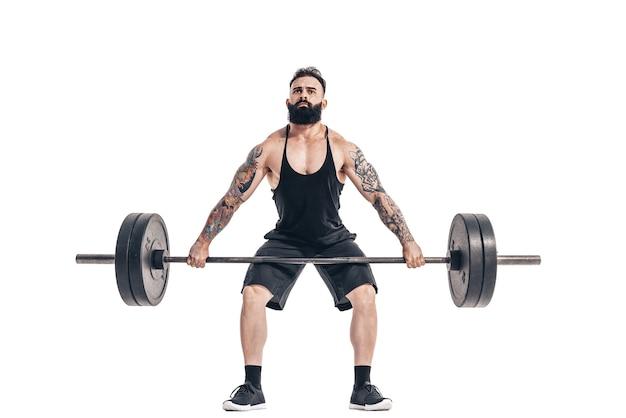 A técnica de fazer um exercício de levantamento terra com uma barra de um musculoso forte tatuado em esportistas barbudos