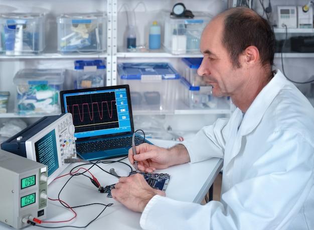 A tecnologia masculina sênior trabalha na instalação de reparo de hardware