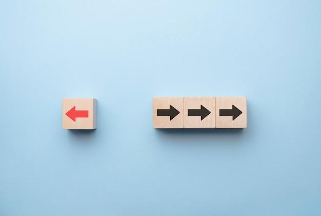 A tela de impressão da seta vermelha em um bloco de madeira muda a direção da direita para a esquerda, que difere das setas pretas