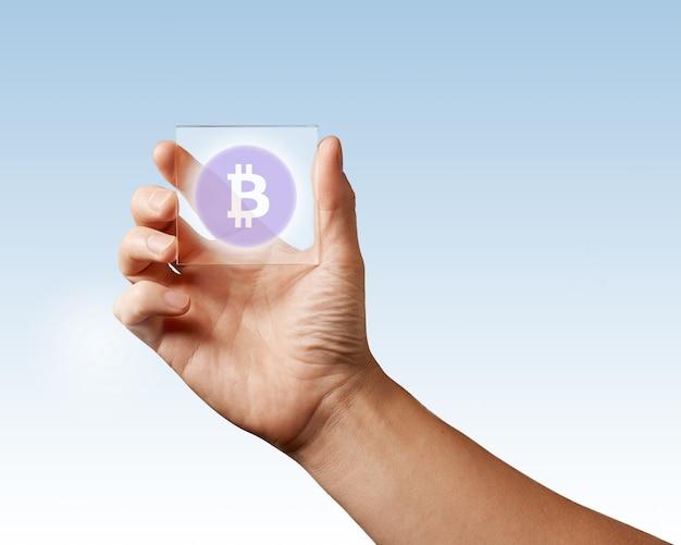 A tela digital transparente é segurada por uma mão masculina com um ícone de bitcoin em uma superfície azul. conceito de negócios, tecnologia e criptomoeda