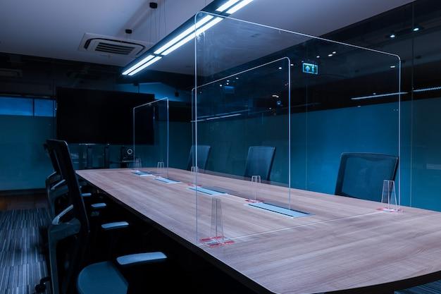 A tela em branco da televisão na sala de reuniões de videoconferência com folha de acrílico transparente separa o centro da mesa de conferência para evitar covid-19