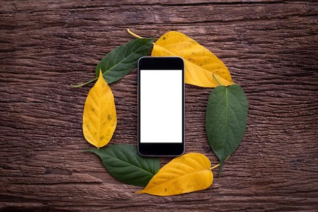 A tela vazia sobre no smartphone, no móbil, no telefone celular e na folha dá um ciclo o fundo do quadro na tabela de madeira.