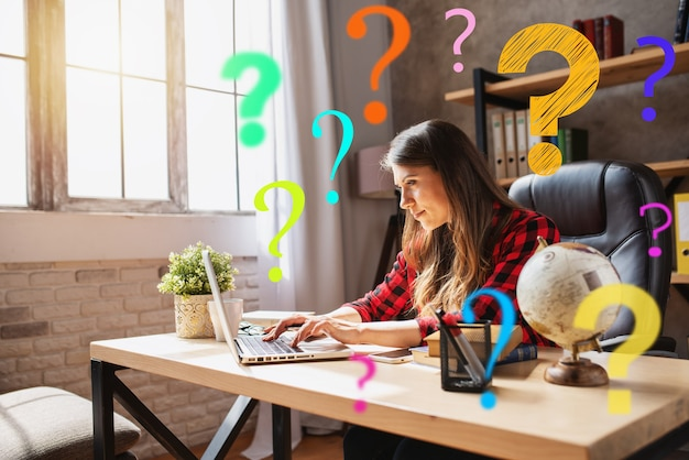 A teletrabalhadora trabalha em casa com um laptop e muitas perguntas.