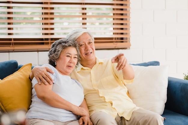 A televisão de observação dos pares idosos asiáticos na sala de visitas em casa, par doce aprecia o momento do amor ao encontrar-se no sofá quando relaxado em casa.