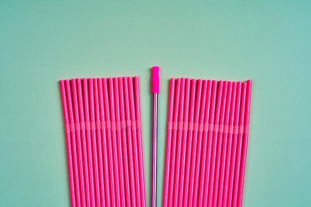 A tendência moderna de cuidar do meio ambiente. canudos reutilizáveis de metal para bebidas entre um pacote de canudos de plástico rosa.