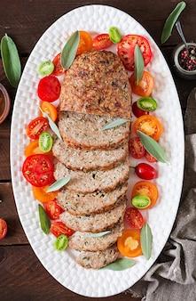 A terra caseiro saboroso cozeu o bolo de carne do peru na placa branca na tabela de madeira. pão de carne americana de alimentos. vista do topo. configuração plana