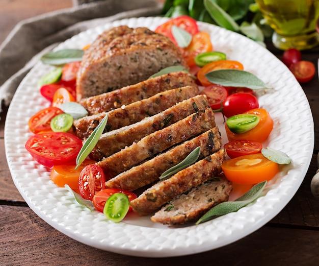 A terra caseiro saboroso cozeu o bolo de carne do peru na placa branca na tabela de madeira. pão de carne americana de alimentos.