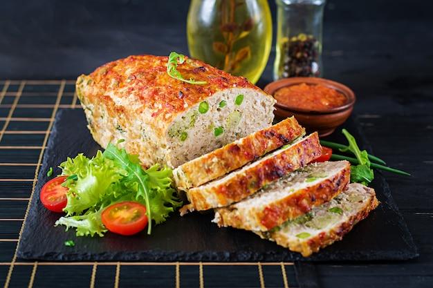 A terra caseiro saboroso cozeu o meatloaf da galinha com ervilhas verdes e brócolis na tabela preta.