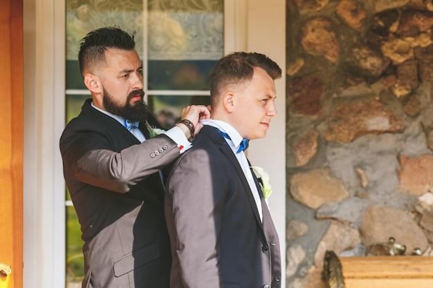A testemunha ajuda a noiva a usar uma jaqueta.