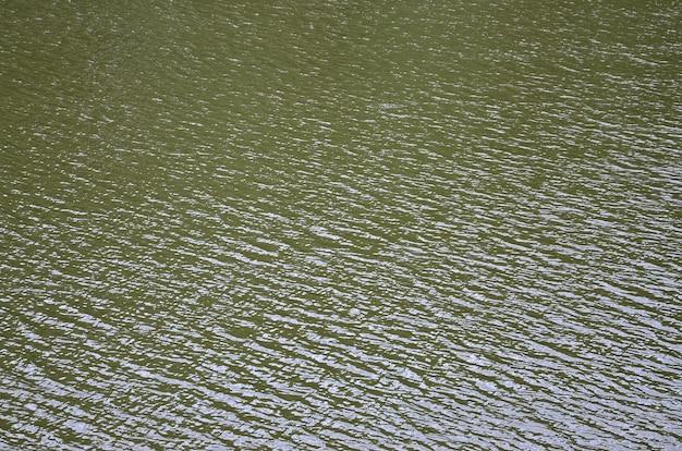 A textura da água do rio escuro sob a influência do vento
