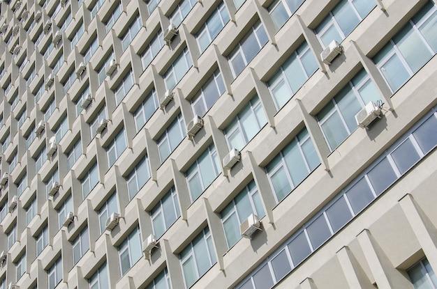 A textura da fachada de um edifício soviético com muitas janelas e aparelhos de ar condicionado