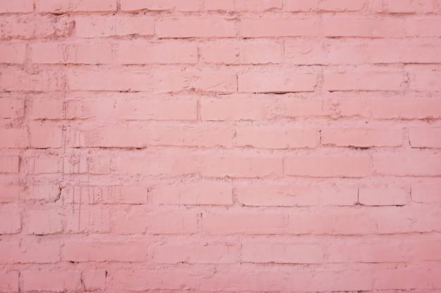 A textura da fachada do edifício de uma parede de tijolos com fileiras de tijolos pintados na cor rosa