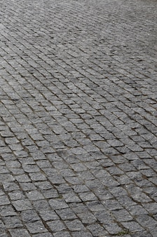 A textura da laje de pavimentação (pedras de pavimentação) de muitas pequenas pedras de uma forma quadrada sob a luz solar brilhante