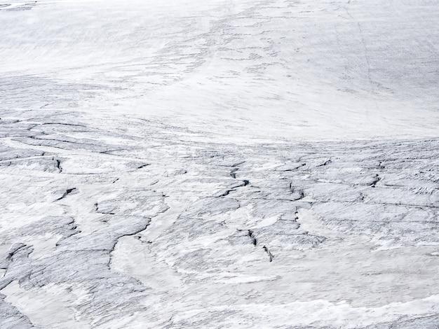 A textura da neve branca, claro-escuro branco. cenário natural mínimo de parede de gelo com rachaduras e arranhões de gelo da geleira.