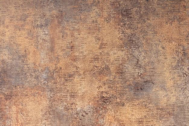 A textura da parede de concreto é coberta com revestimento marrom e fundo de rachaduras