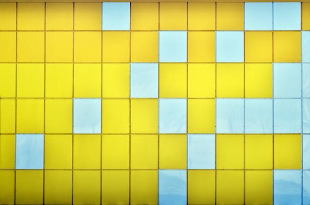 A textura da parede de metal, emoldurada na forma de quadrados coloridos de duas cores.