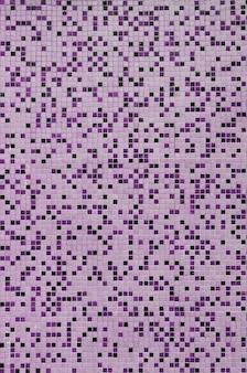 A textura da parede, decorada com um mosaico de vários pequenos azulejos quadrados.