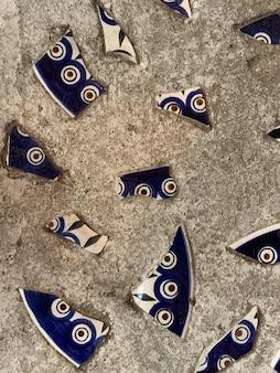 A textura da parede, o chão é cinza com pedaços de porcelana azul quebrada com um padrão.