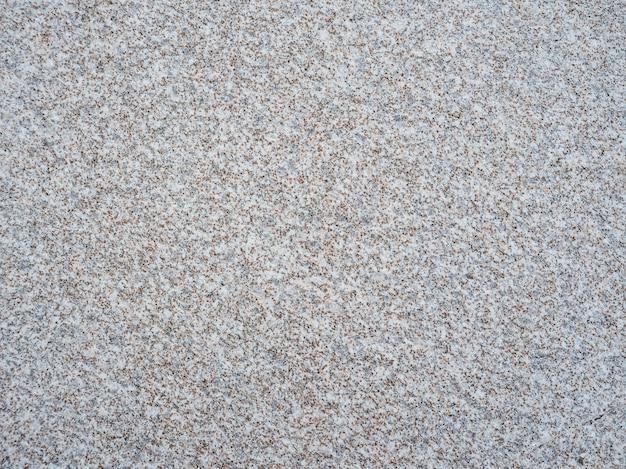 A textura da pedra artificial cinza entremeada por lascas de granito.