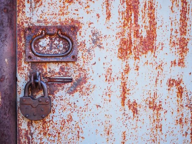 A textura da porta e a fechadura do velho metal enferrujado vermelho