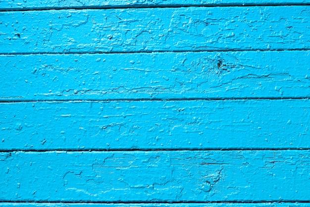 A textura das pranchas de madeira, pintadas com tinta azul clara, localmente descascadas.