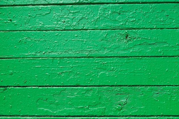 A textura das pranchas de madeira pintadas com tinta verde, localmente descascadas.