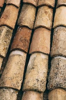A textura das velhas telhas marrons no telhado do edifício