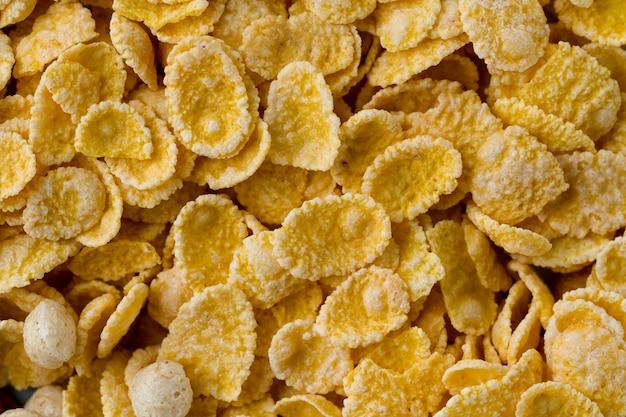 A textura de flocos de milho amarelos secos, geados, vitrificados para cereais toma o café da manhã.