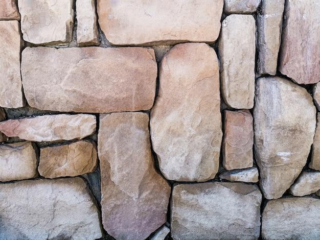 A textura de grandes pedras em tons de bege. fundo abstrato da parede de pedra para designers.