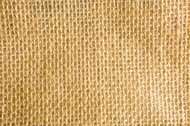 A textura de serapilheira, trama áspera em uma gaiola feita de fibra natural, cor amarelo-marrom. copyspace, close-up